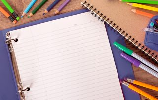 example of school supplies like open 3-ring binder, pens and pencils
