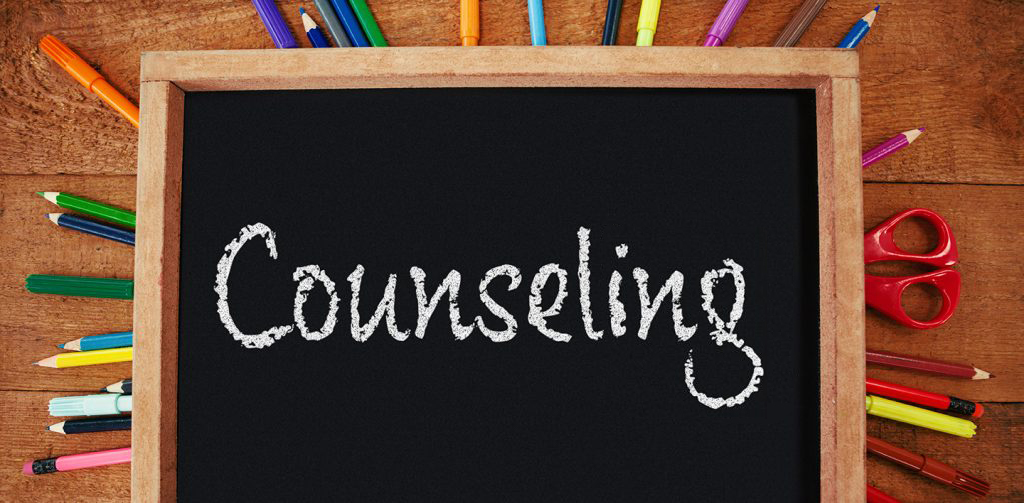 the word counseling written on a chalkboard surrounded by colorful pencils